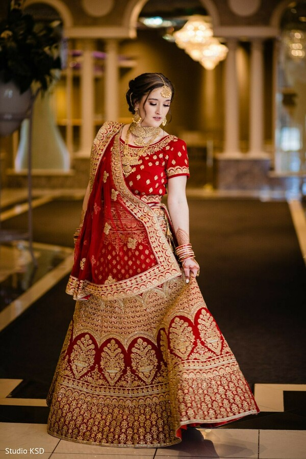 Indian bride wearing her red and golden lehenga saree.