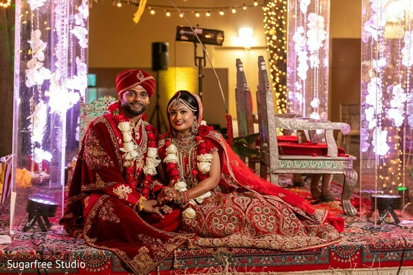 Indian couple wearing their ceremony wedding red outfits.