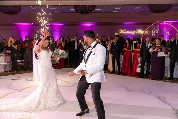Indian couple dancing at wedding reception stage.