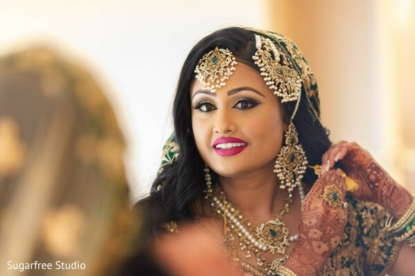 Indian bride putting her wedding jewelry on.