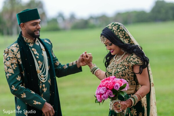 Indian couple posing outdoors on their green wedding outfits.