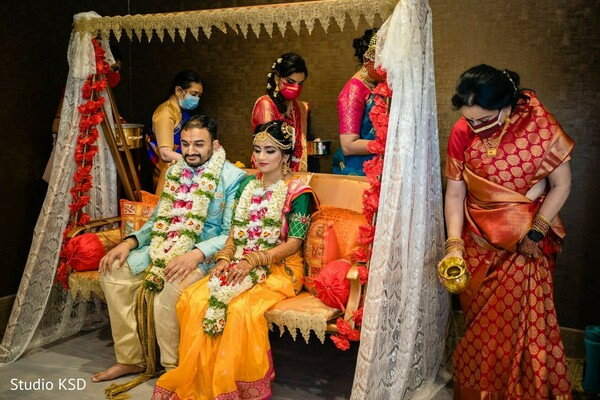 Indian couple seated on a swing sofa during wedding ritual.