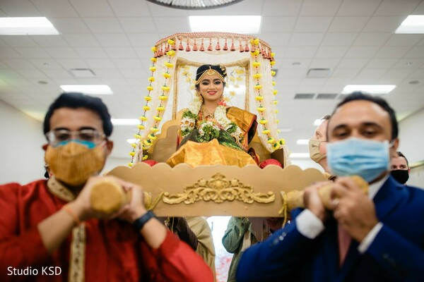 Indian bride making her entrance on a doli to the wedding ceremony.