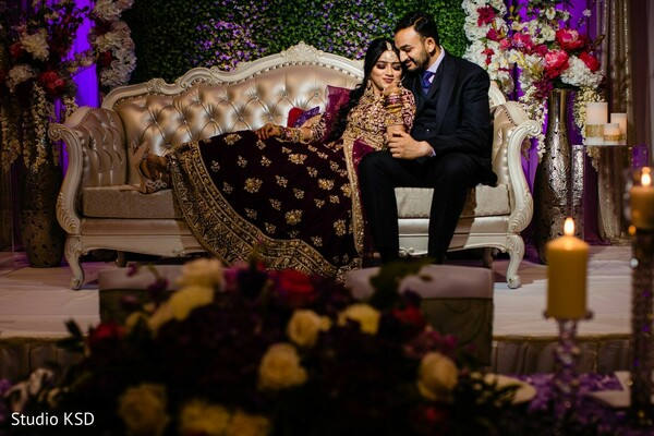 Indian couple posing at wedding reception stage.