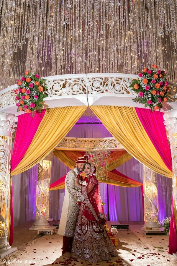 Indian couple posing under the stunning mandap.