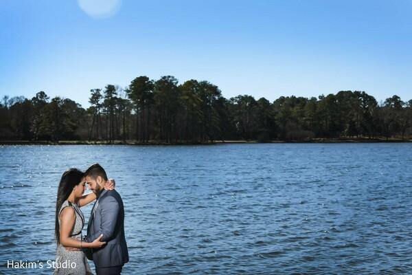 Indian couple posing next to a lake.