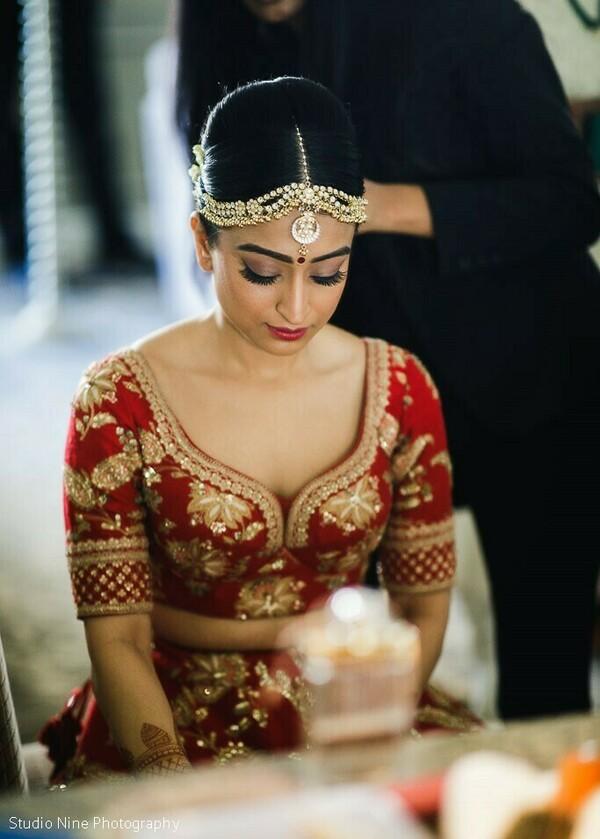 Indian bride wearing her wedding hair accessories.