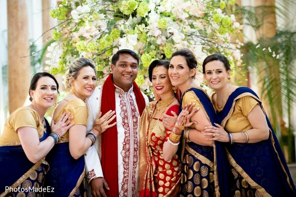 Indian couple posing with bridesmaids.