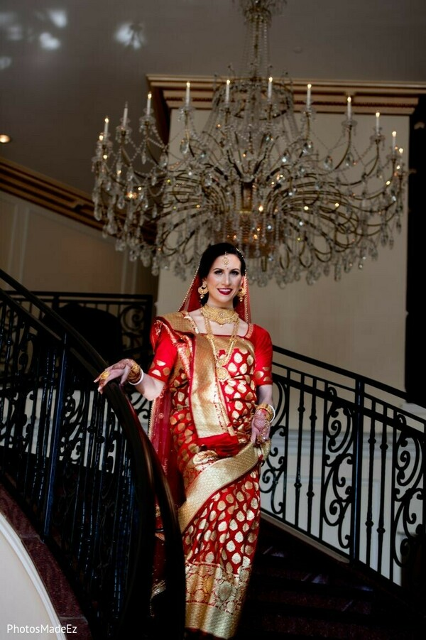 Indian bride walking down the stairs on her red and golden saree.