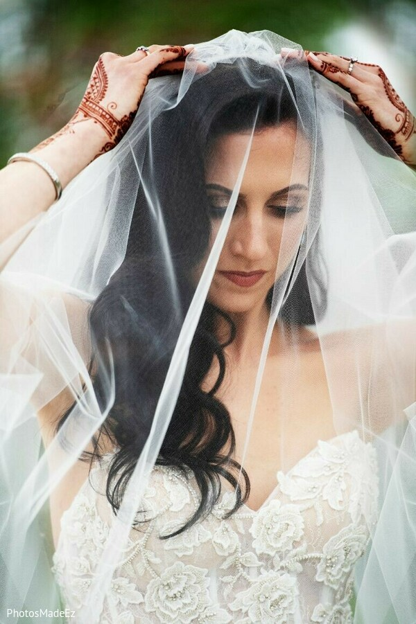 Indian bride putting her white veil on.