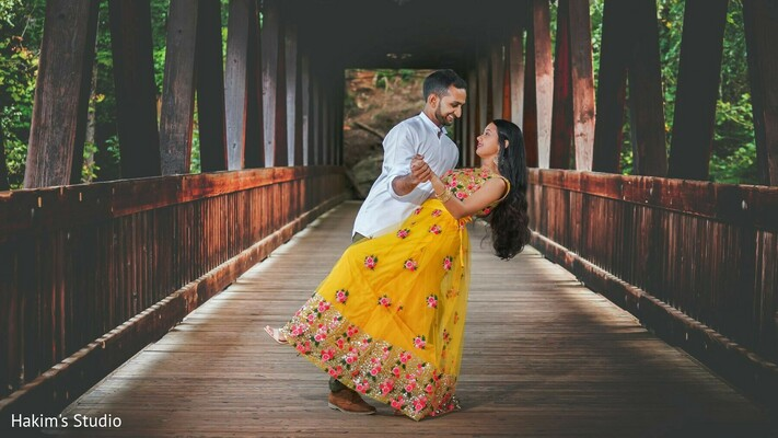 Indian couple posing on a wooden bridge.