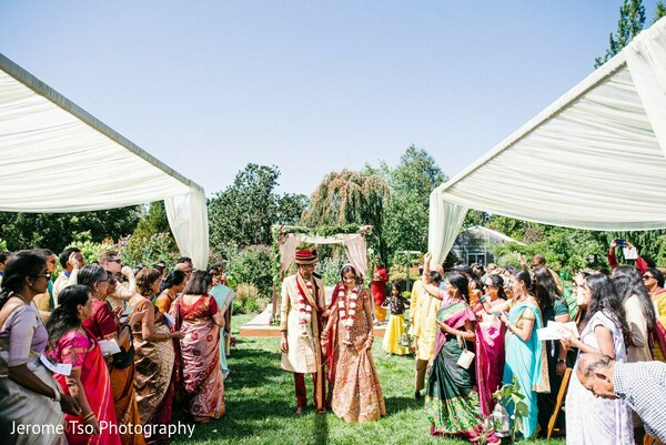 Indian bride and groom walking out from the ceremony aisle