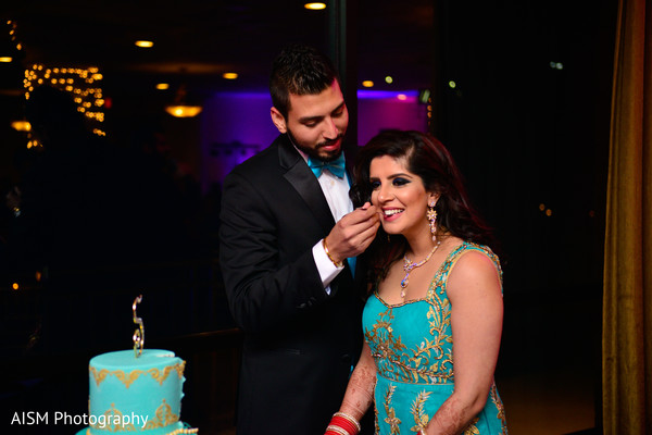 Indian Bride and Groom Cutting Reception Cake in Chantilly, VA Hindu & Sikh Wedding by AISM Photography