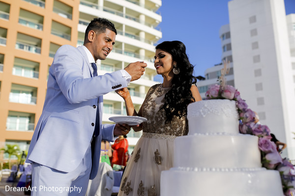 Lovely Indian couple cutting their delicious cake in Cancun, MX Indian Wedding by DreamArt Photography