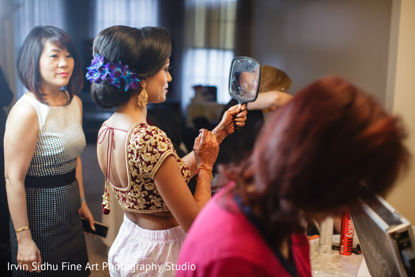 Indian bride checking her make up while getting ready. in Brampton, ON Indian Wedding by Irvin Sidhu Fine Art Photography Studio