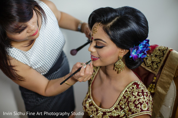 Make up artist giving the final touches to indian bride's make up