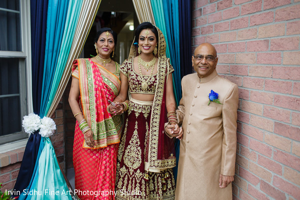 Indian bride waiting with her parents outside her home. in Brampton, ON Indian Wedding by Irvin Sidhu Fine Art Photography Studio