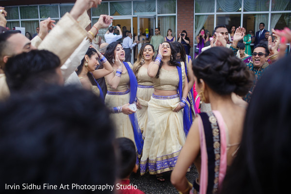 Bridesmaids singing during the baraat. in Brampton, ON Indian Wedding by Irvin Sidhu Fine Art Photography Studio