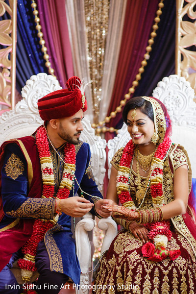 Excited indian groom giving his bride the wedding ring in Brampton, ON Indian Wedding by Irvin Sidhu Fine Art Photography Studio