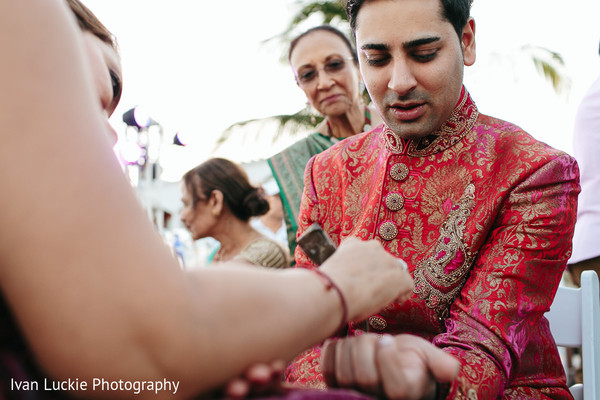 Indian groom getting a henna tattoo in his arm. in Playa del Carmen Playa del Carmen Destination Indian Wedding by Ivan Luckie Photography