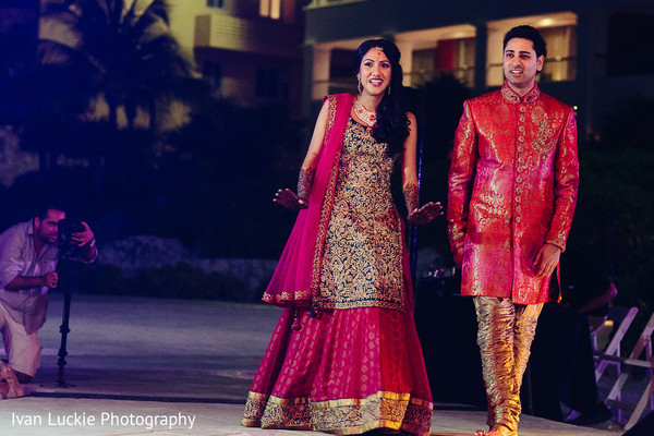 Indian bride and groom in red making their entrance to their mehndi party. in Playa del Carmen Playa del Carmen Destination Indian Wedding by Ivan Luckie Photography