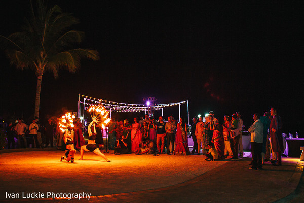 Female fire dancers entertaining the mehndi party guests. in Playa del Carmen Playa del Carmen Destination Indian Wedding by Ivan Luckie Photography