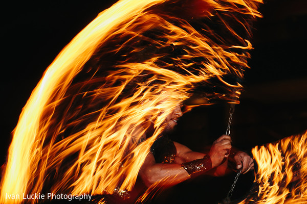 Curtain of fire made by a fire dancer at the mehndhi party, in Playa del Carmen Playa del Carmen Destination Indian Wedding by Ivan Luckie Photography