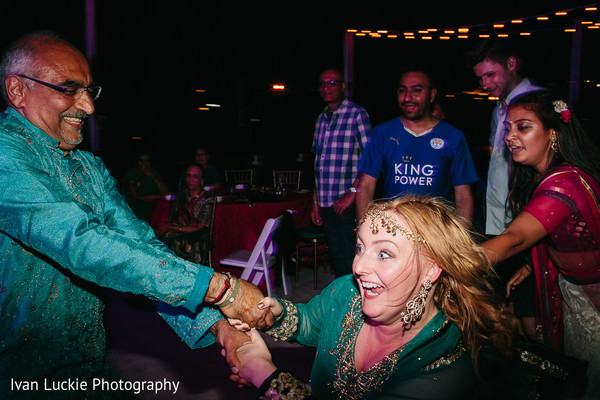 Guests having a blast during the mehndi party night. in Playa del Carmen Playa del Carmen Destination Indian Wedding by Ivan Luckie Photography