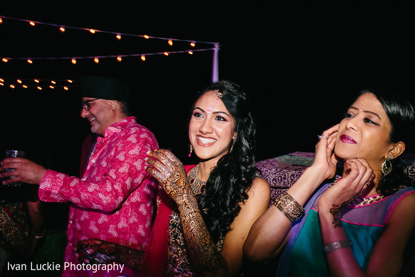 Indian bride smiling and watching her guests have fun at her mehndi night. in Playa del Carmen Playa del Carmen Destination Indian Wedding by Ivan Luckie Photography