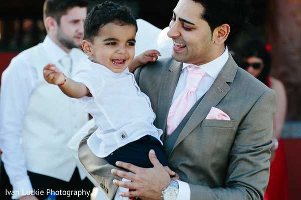 Groom sharing with the youngest guest. in Playa del Carmen Playa del Carmen Destination Indian Wedding by Ivan Luckie Photography