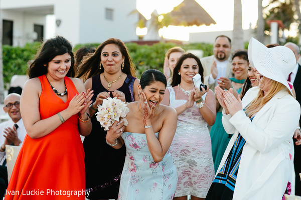 Fortunate single lady getting the bride's bouquet. in Playa del Carmen Playa del Carmen Destination Indian Wedding by Ivan Luckie Photography