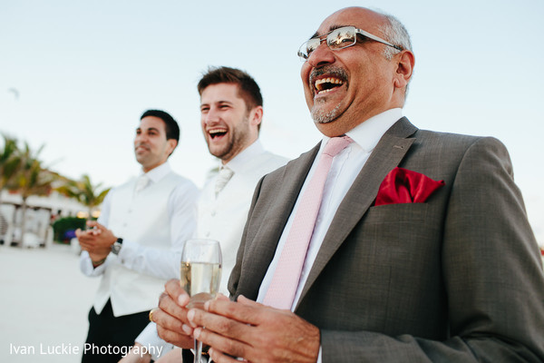 Guests drinking champagne after the outdoor exchange of rings ceremony. in Playa del Carmen Playa del Carmen Destination Indian Wedding by Ivan Luckie Photography