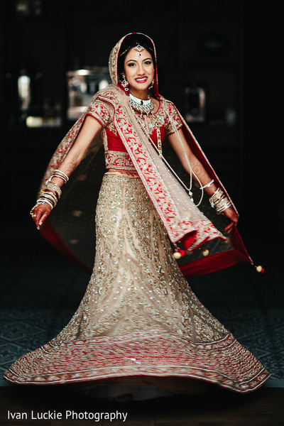Beautiful indian bride in her gold and red wedding lengha. in Playa del Carmen Playa del Carmen Destination Indian Wedding by Ivan Luckie Photography