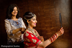 Lovely indian bride checking her hair and make up.