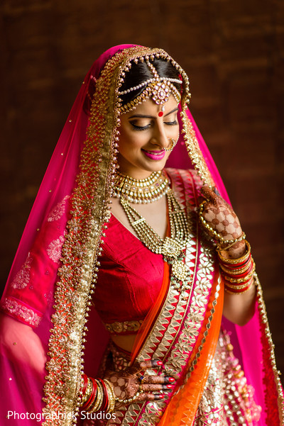 Lovely indian bride posing in her hot pink wedding attire. in Alexandria, VA Indian Wedding by Photographick Studios