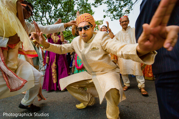 Guests and groom dancing at the baraat. in Alexandria, VA Indian Wedding by Photographick Studios