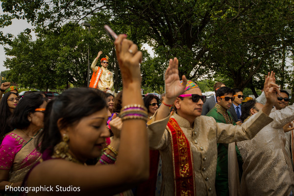 Guests escorting groom during baraat procession. in Alexandria, VA Indian Wedding by Photographick Studios