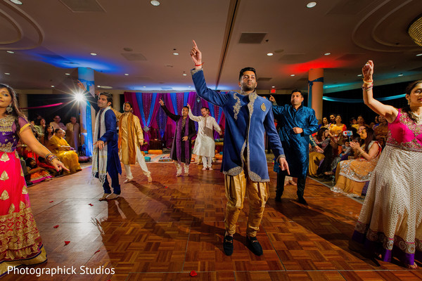 Indian groom dancing at a pre-wedding celebration. in Alexandria, VA Indian Wedding by Photographick Studios