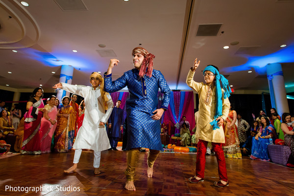 Bride and groom's family members performing during a pre -wedding celebration. in Alexandria, VA Indian Wedding by Photographick Studios