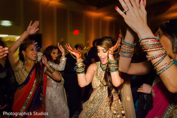 Happy indian bride dancing and clapping at her wedding reception. in Alexandria, VA Indian Wedding by Photographick Studios