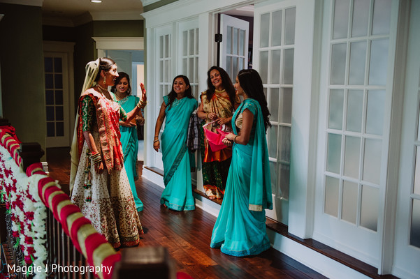 Indian bride showing her outfit to her bridesmaids. in Bethlehem, Pennsylvania Indian Wedding by Maggie J Photography
