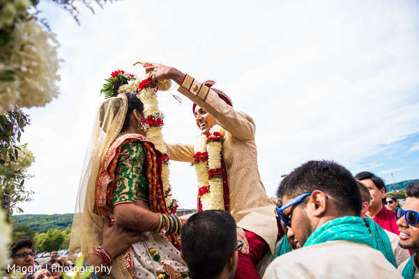 Indian bride and groom exchanging garlands. in Bethlehem, Pennsylvania Indian Wedding by Maggie J Photography