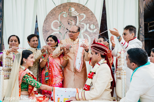 See this Indian bride and groom being united by their family members. in Bethlehem, Pennsylvania Indian Wedding by Maggie J Photography