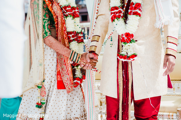 Cute shot of indian bride and groom holding hands. in Bethlehem, Pennsylvania Indian Wedding by Maggie J Photography