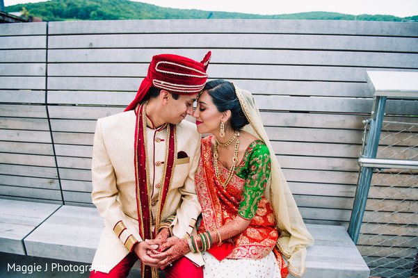 Romantic photo of indian bride and groom in red, gold and white outfits. in Bethlehem, Pennsylvania Indian Wedding by Maggie J Photography