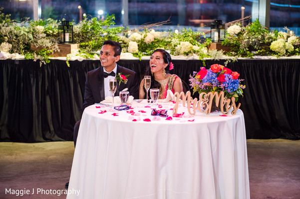 Beautiful indian bride and groom sitting at their main table during wedding reception. in Bethlehem, Pennsylvania Indian Wedding by Maggie J Photography