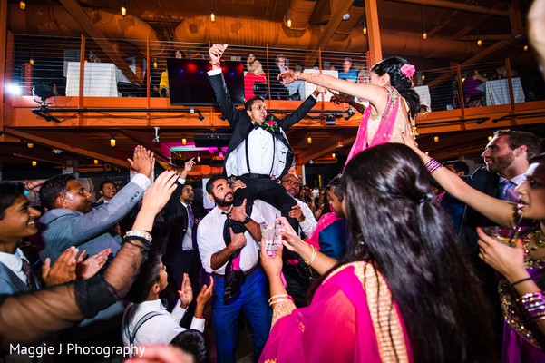Bride and groom being carried by family members at their wedding reception. in Bethlehem, Pennsylvania Indian Wedding by Maggie J Photography