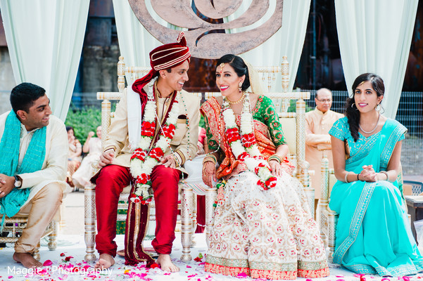 Indian bride and groom chat between them during traditional wedding ceremony. in Bethlehem, Pennsylvania Indian Wedding by Maggie J Photography