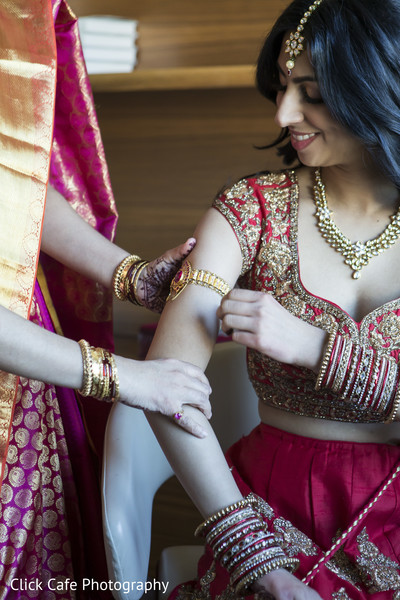 Indian bride adjusting her jewelry. in Jersey City, NJ Indian Wedding by Click Café Photography