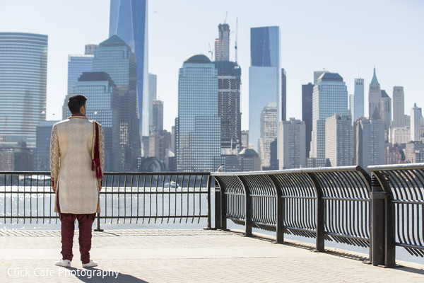Indian groom looking at the skyscrapers and waiting to see his beautiful bride. in Jersey City, NJ Indian Wedding by Click Café Photography